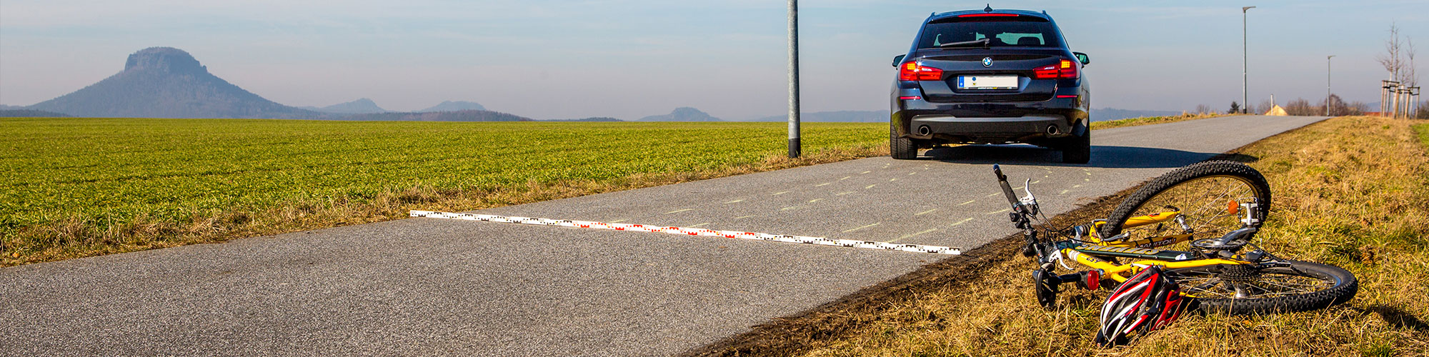 Im Vordergrund liegt ein Fahrrad neben der Fahrbahn auf der Straße, ein Stück weiter auf der Straße steht leicht schräg ein Auto, auf der Straße liegt eine Messlatte und die Spuren des Autos wurden mit Kreide markiert