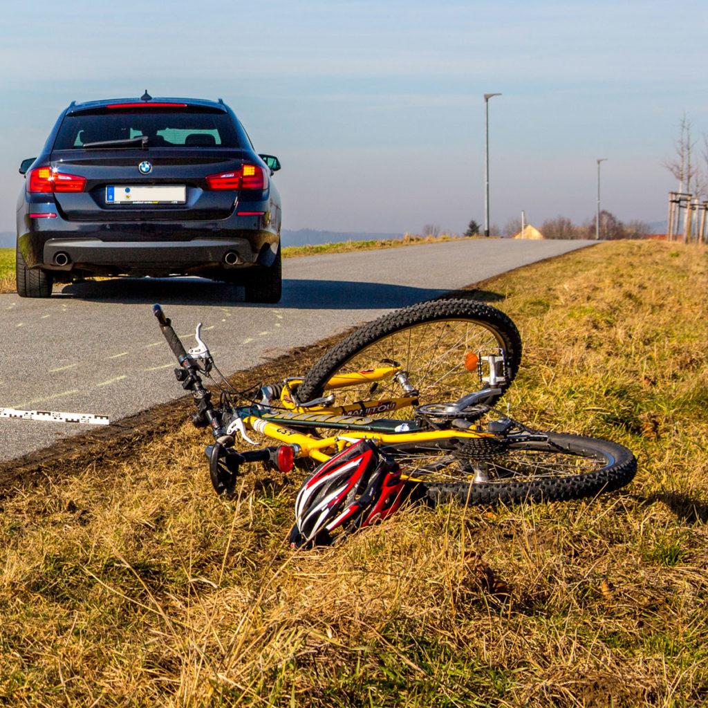 Im Vordergrund liegt ein Fahrrad zusammen mit einem Fahrradhelm neben der Straße auf dem Rasen, ein Stück weiter hinten auf der Straße steht leicht schräg ein Auto mit eingeschaltetem Warnblinklicht