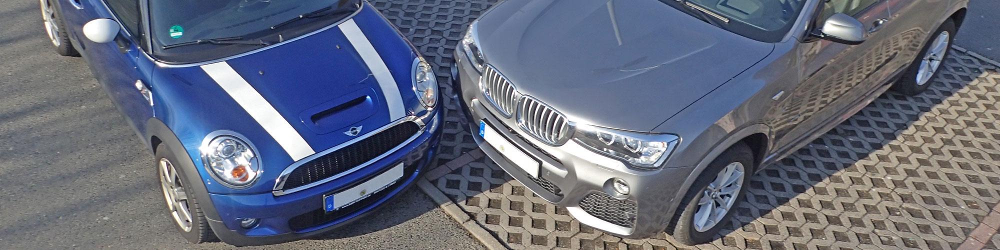 Zwei Autos stehen im rechten Winkel sehr nah beieinander auf einem Parkplatz