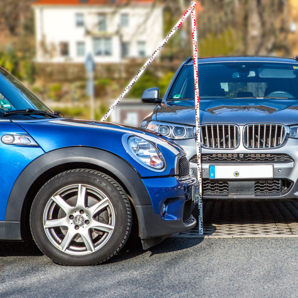 Zwei Autos die im 90°-Winkel zueinander stehen, Messlatte für die Überprüfung der Kompatibilität der Schäden