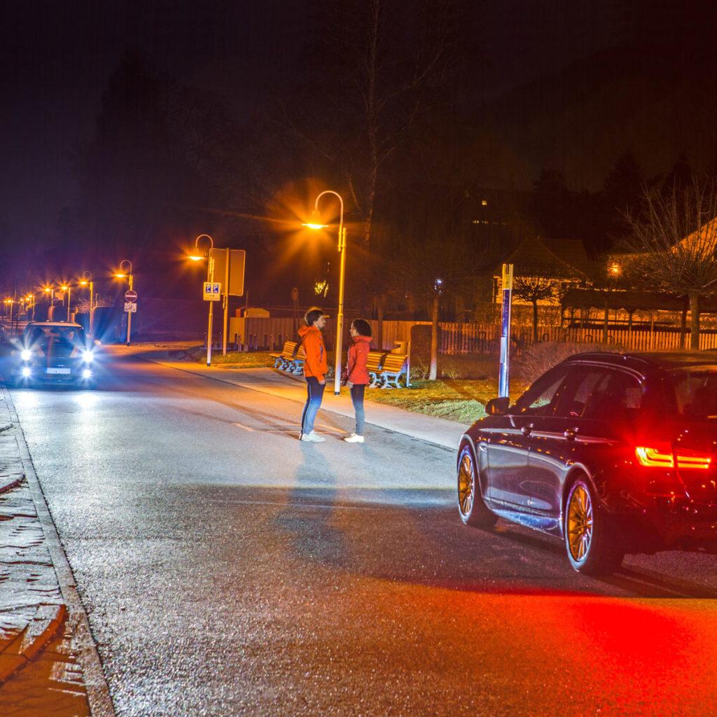 Lichttechnikuntersuchung in der Nacht: Bei Dunkelheit stehen auf einer Straße ein Mann und eine Frau sich gegenüber ein Stück vor einem Auto, auf der Gegenfahrbahn kommt ebenfalls ein Auto gefahren, ein kleiner Fußweg führt neben der Straße, der beleuchtet ist mit Laternen