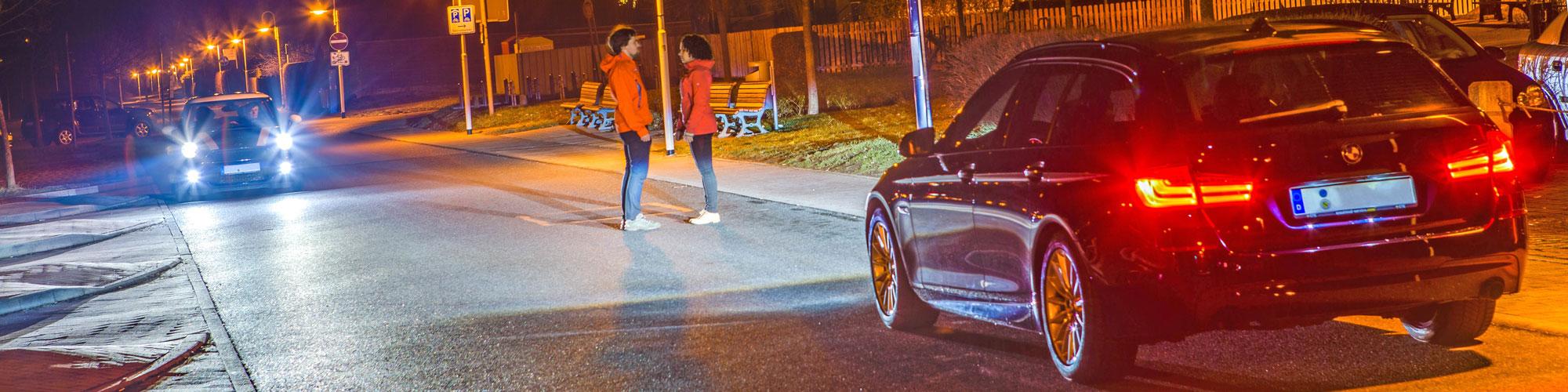 Unfallanalyse bei Nacht: Auf einer Straße stehen sich ein Mann und eine Frau bei Nacht gegenüber, aus beiden Richtungen kommen Autos mit eingeschaltetem Licht, neben der Straße befindet sch ein beleuchteter Fußweg