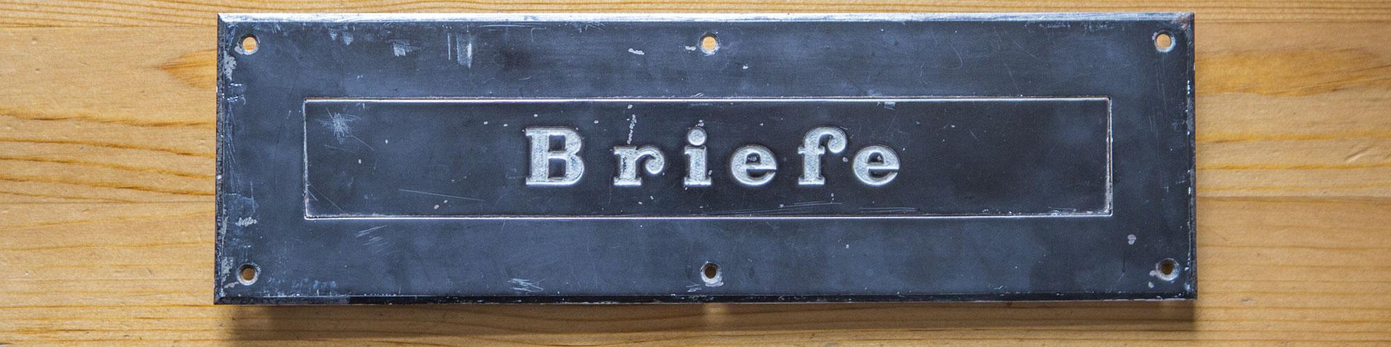 Alter Briefschlitz schwarz, auf der Klappe steht das Wort Briefe