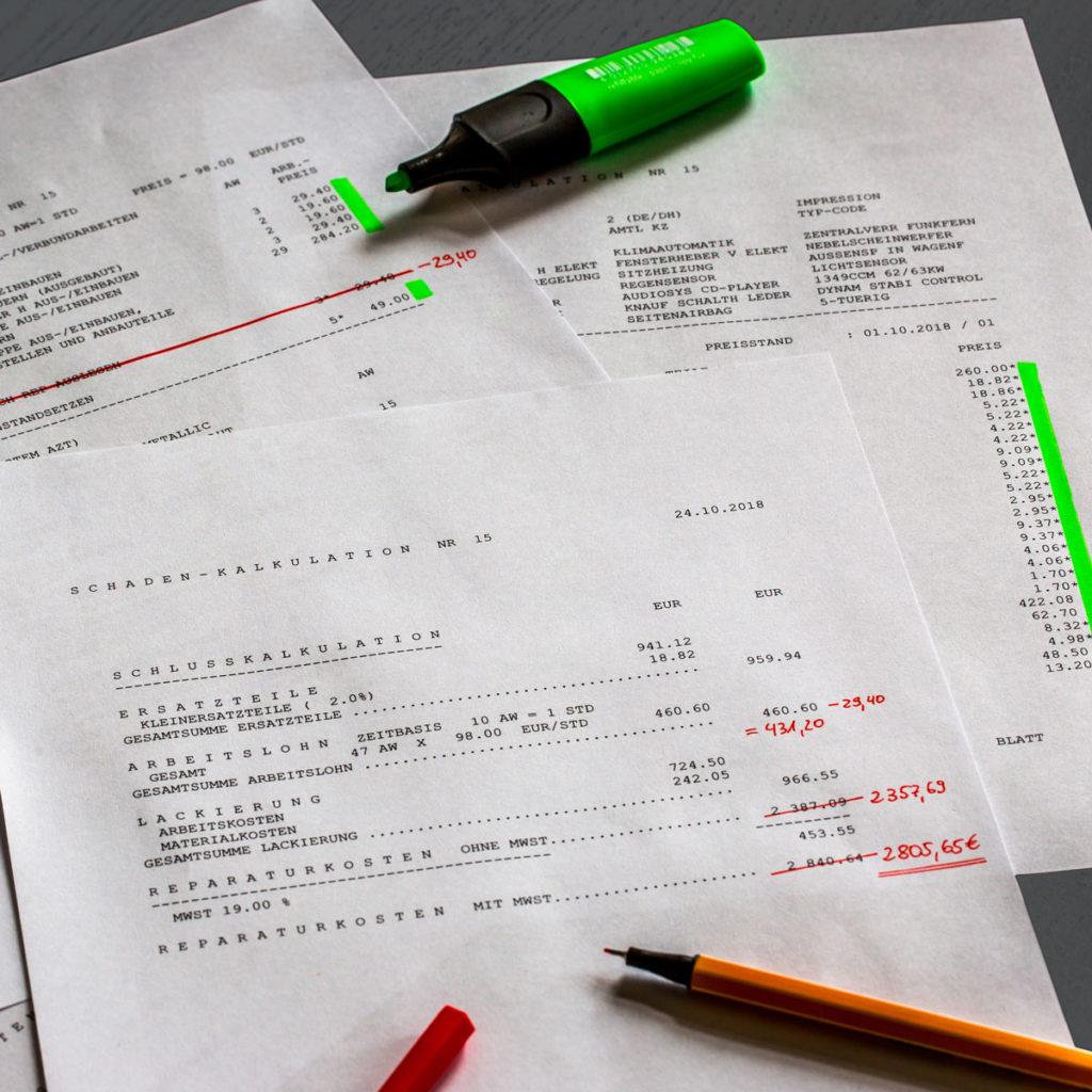 Überprüfung eines Schadengutachtens: Auf einem Tisch liegt ein Schadengutachten, auf dem verschiedene Angaben rot und grün angestrichen sind, ein grüner Marker und ein roter Feinline liegen auf den Ausdrucken