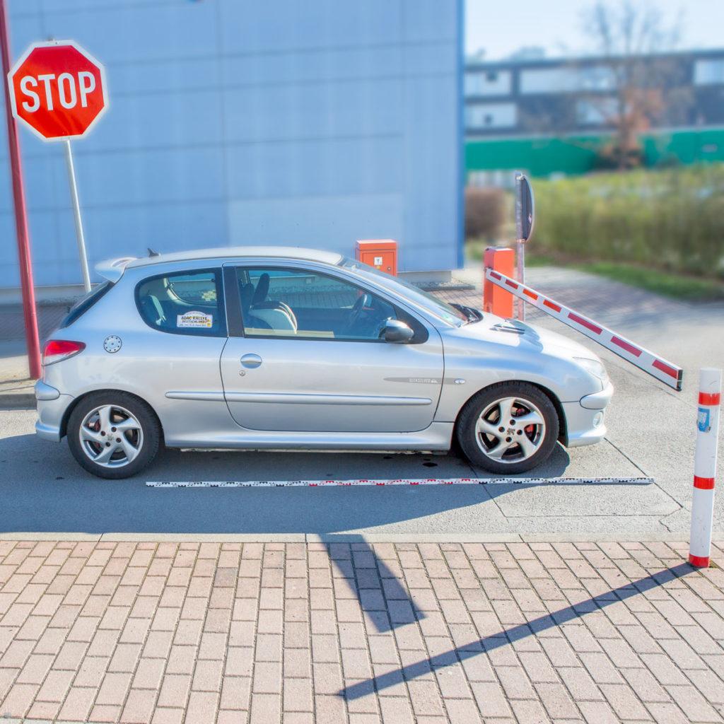 Ein kleines Auto steht vor einer Schrankenanlage, die Schranke ist unten und die Motorhaube ragt unter der Schrank ein Stück hinaus, vor dem Auto liegt eine Messlatte auf der Straße