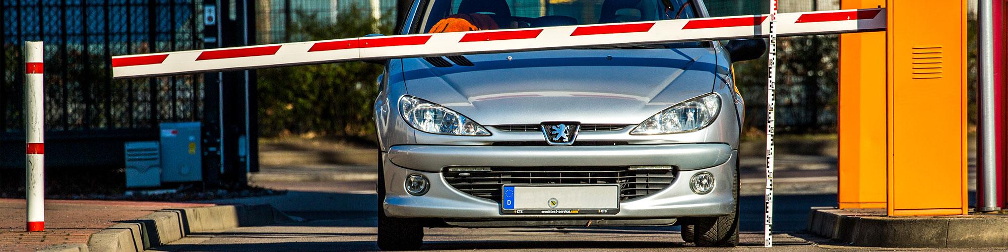 Ein Auto steht vor einer Schranke und ragt mit der Motorhaube uter der Schranke hinaus, fotografiert von vorn