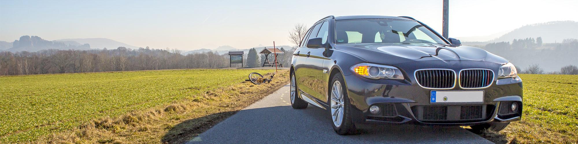 Im Vordergrund steht ein Auto leicht schräg auf einer schmalen Straße, dahinter liegt auf der linken Seite ein Fahrrad neben der Fahrbahn auf dem Rasen